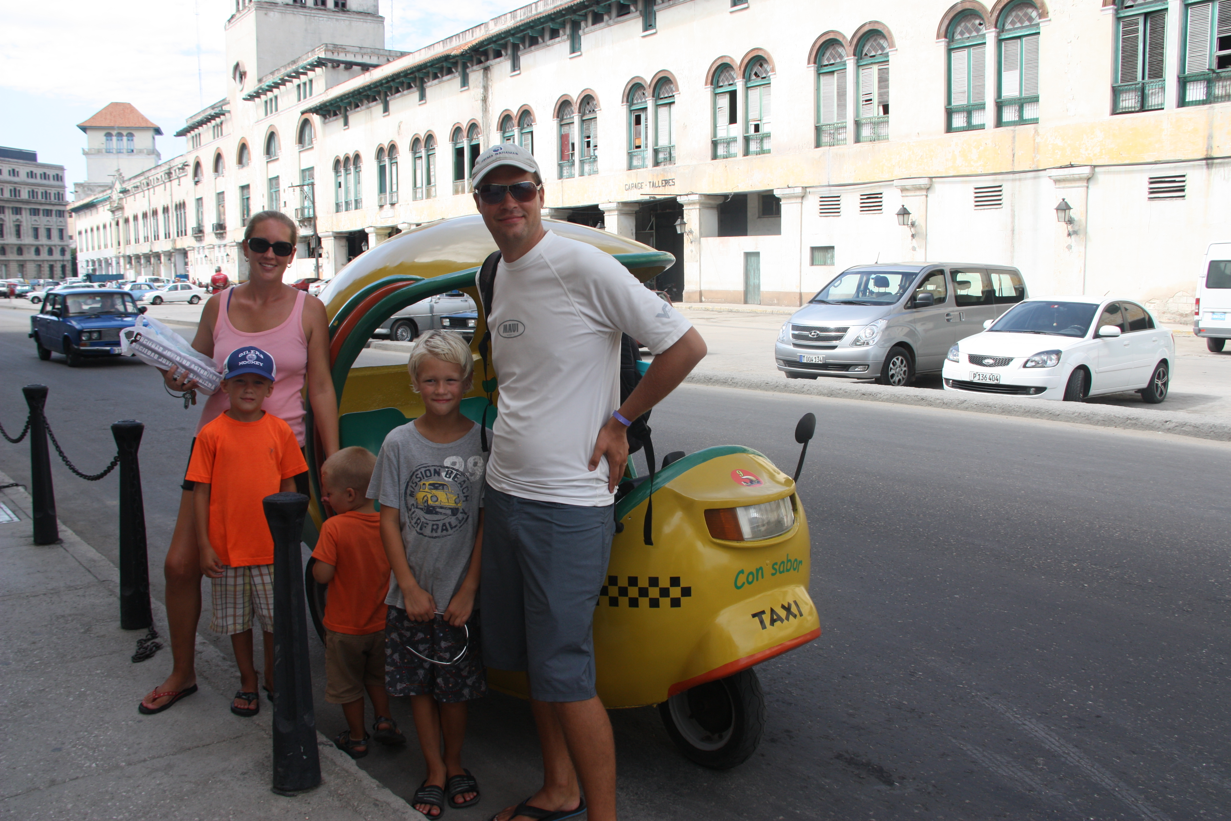 The family in front of a Coco Taxi