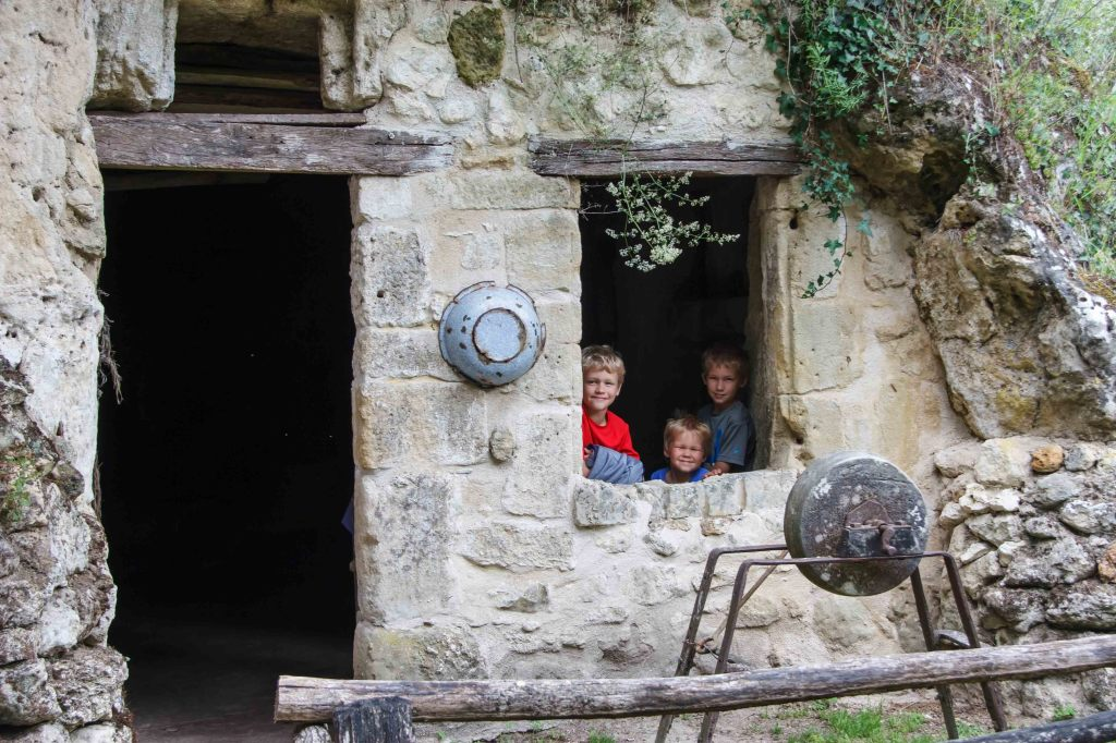 Peasant boys, peeking out the window of their cave home.
